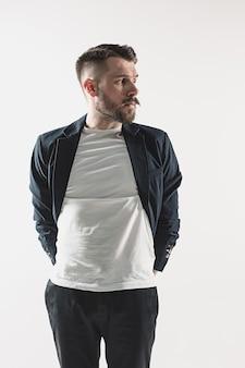 Retrato de jovem bonito elegante no estúdio contra branco. homem vestindo jaqueta