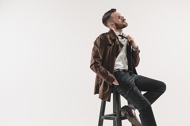 Retrato de jovem bonito elegante sentado no estúdio contra branco. homem vestindo jaqueta