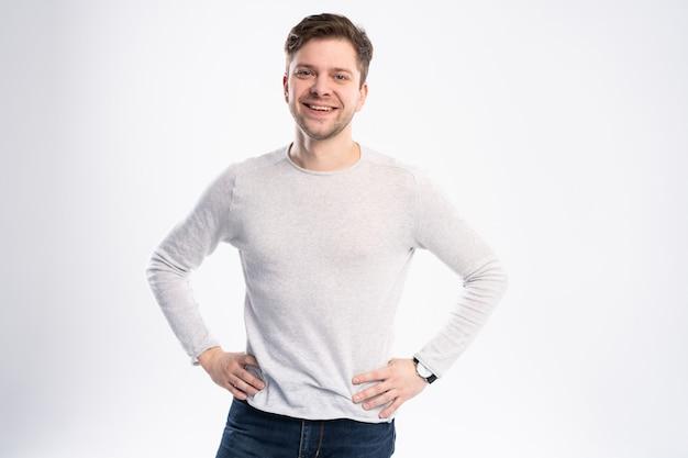 Retrato de jovem bonito em camisa casual sorrindo em pé contra um fundo branco