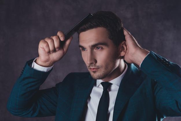 Retrato de jovem bonito em terno preto penteando o cabelo