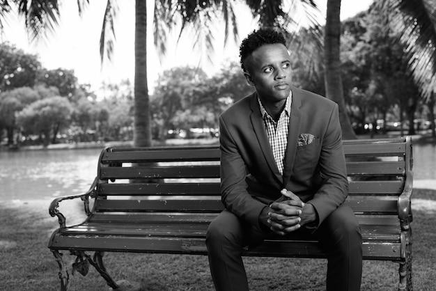 Retrato de jovem bonito empresário africano vestindo terno enquanto relaxa no parque em preto e branco