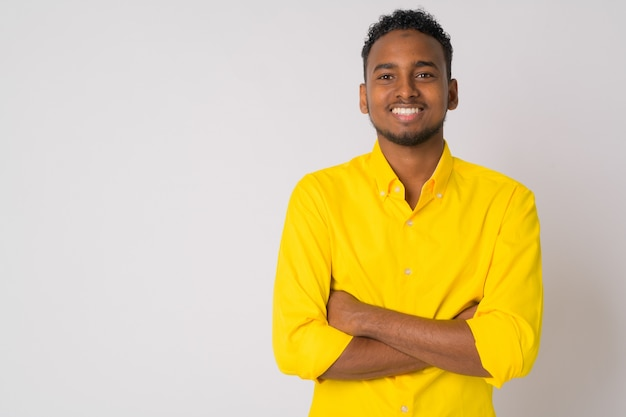 Retrato de jovem bonito empresário africano vestindo uma camisa amarela contra uma parede branca