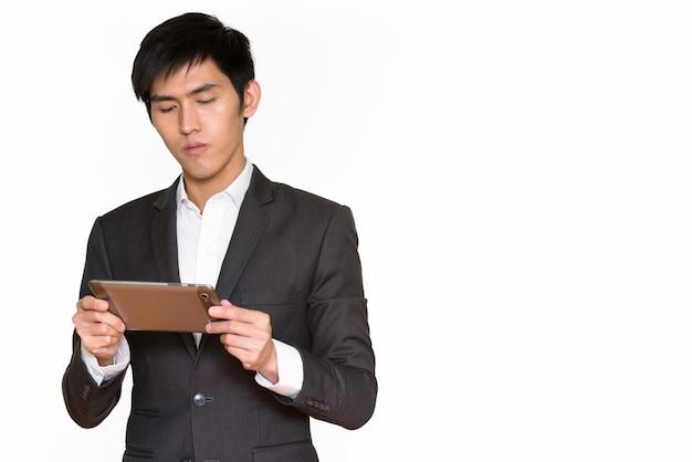 Retrato de jovem bonito empresário asiático usando tablet digital isolado contra uma parede branca