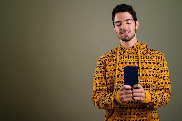 Retrato de jovem bonito feliz usando o telefone