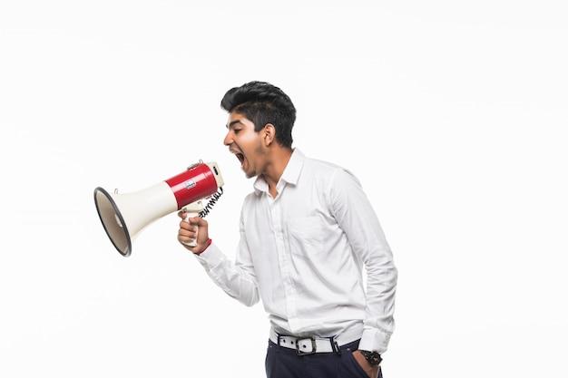 Retrato de jovem bonito gritando usando o megafone isolado na parede branca