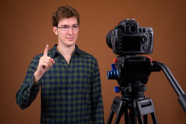 Retrato de jovem bonito hippie fazendo um vlog com a câmera