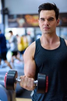 Retrato de jovem bonito homem musculoso se exercitando na academia