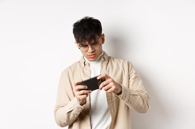 Retrato de jovem bonito jogando videogame no celular, incline o smartphone para jogar corridas, de pé na parede branca.
