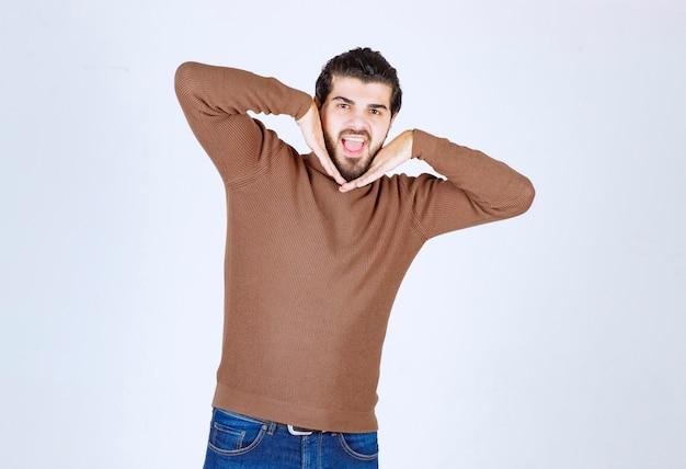 Retrato de jovem bonito, levantando as palmas das mãos perto do rosto e sorrindo contra um fundo branco cinza. foto de alta qualidade