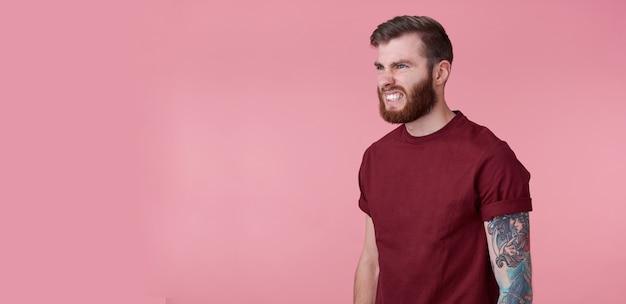 Retrato de jovem bonito malvado homem barbudo vermelho em t-shirt em branco, parece agressivo e chocado, fica sobre um fundo rosa, ooks para copiar o espaço no lado esquerdo.