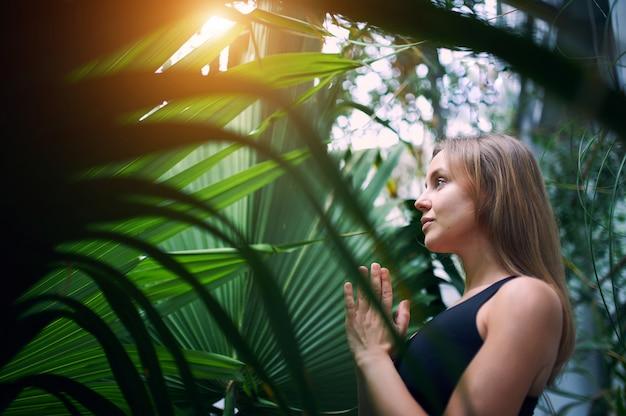 Retrato de jovem bonito meditando e fazendo a mão namastê na selva.