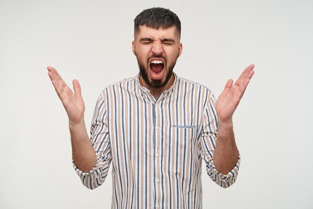 Retrato de jovem bonito, morena, barbudo, homem, mantendo as mãos levantadas enquanto grita com a boca escancarada, vestindo roupas casuais em pé sobre uma parede branca