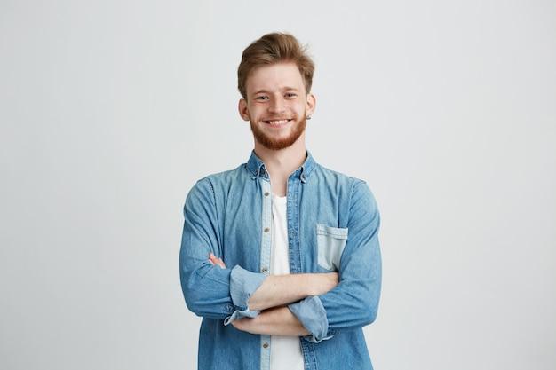 Retrato de jovem bonito na camisa jeans, sorrindo com braços cruzados.