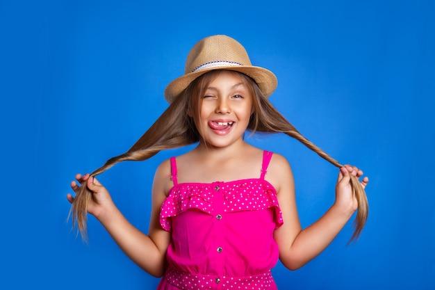 Retrato de jovem bonito no vestido rosa e chapéu se divertindo. férias de verão e o conceito de viagens