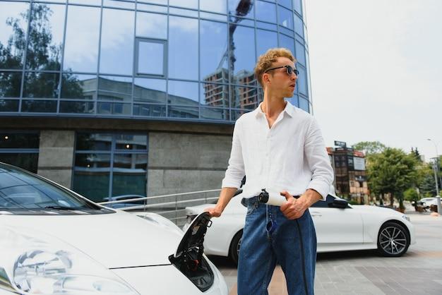 Retrato de jovem bonito no vestuário desportivo, de pé na estação de carregamento. conceito de carro elétrico ecológico