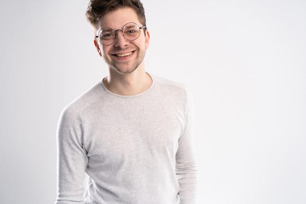 Retrato de jovem bonito olhando diretamente com um sorriso em pé contra o branco