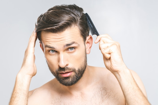 Retrato de jovem bonito, penteando o cabelo no banheiro. isolado sobre o fundo cinza.