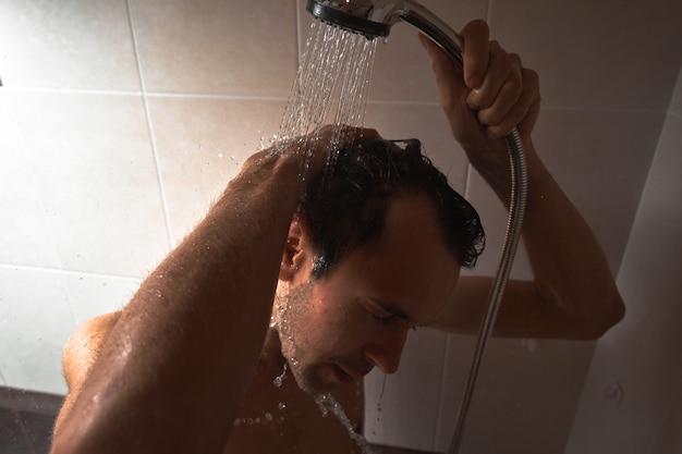 Retrato de jovem bonito se lavando com gel de banho, ensaboando a cabeça com shampoo no banheiro em casa close-up