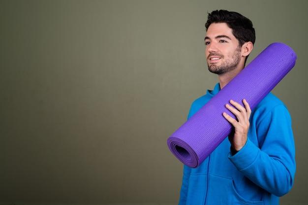 Retrato de jovem bonito segurando o tapete de ioga pronto para a academia