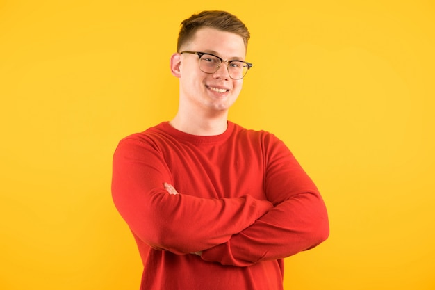 Retrato, de, jovem, bonito, sorrindo, sujeito, em, camisola vermelha, com, braços cruzaram, ligado, amarela