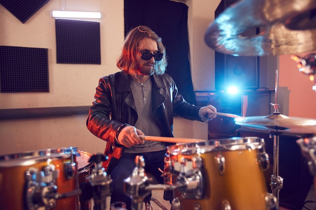 Retrato de jovem bonito tocando bateria durante show de música ou ensaio em estúdio