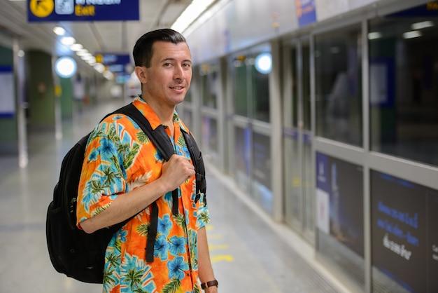 Retrato de jovem bonito turista na estação de metrô da cidade