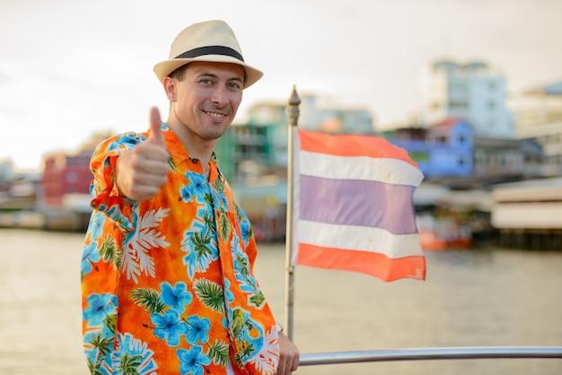 Retrato de jovem bonito turista no cais, vista do rio na cidade de bangkok