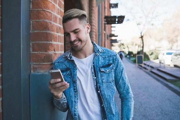 Retrato de jovem bonito usando seu telefone celular ao ar livre na rua. conceito de comunicação.
