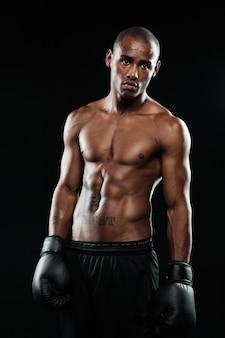 Retrato de jovem boxeador afro-americano bonito em luvas