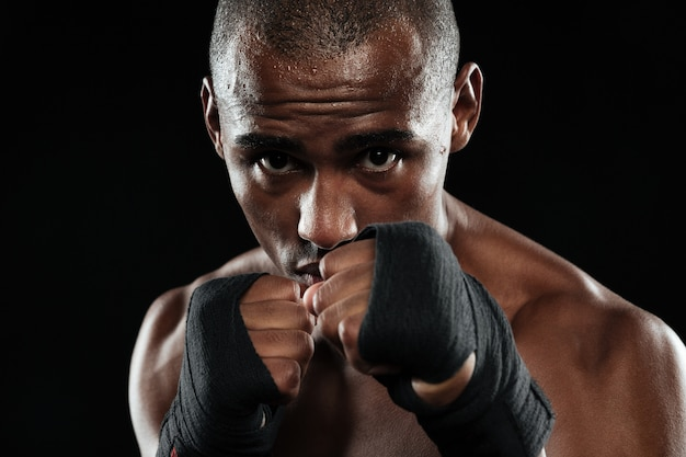 Retrato de jovem boxeador afro-americano, mostrando os punhos
