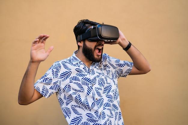 Retrato de jovem brincando com óculos de fone de ouvido vr de realidade virtual contra o espaço amarelo. dispositivo de óculos de fone de ouvido vr. conceito de tecnologia.