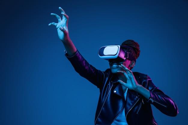 Retrato de jovem brincando com óculos vr em luz de néon