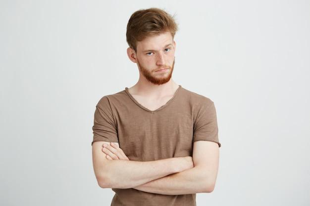 Retrato de jovem brutal com barba com braços cruzados.