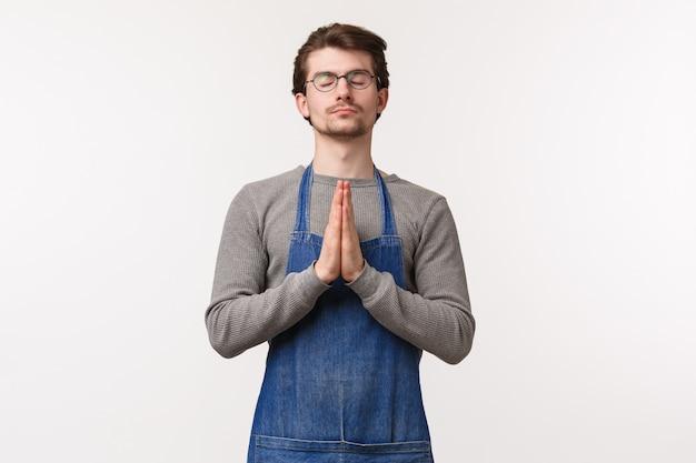 Retrato de jovem calmo e relaxado de avental, preparando-se, relaxando ou liberando o estresse durante a meditação, feche os olhos e dê as mãos em oração, suplicando ou suplicando, parede branca