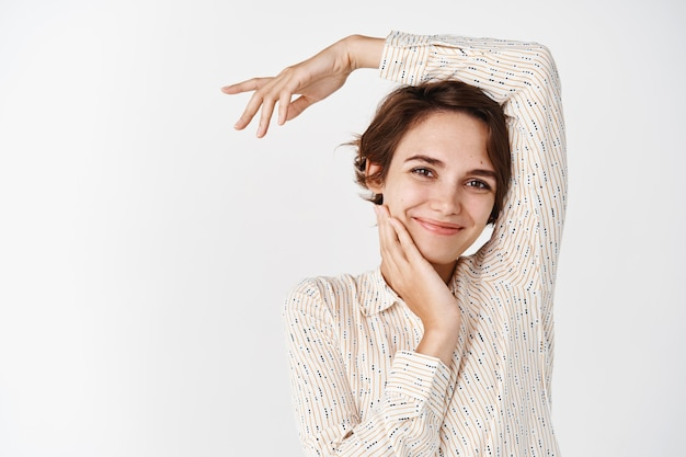 Retrato de jovem cândido em blusa, sorrindo e tocando rosto limpo sem manchas, conceito de beleza e cuidados com a pele, parecendo feliz e relaxado, apoiando o braço na cabeça