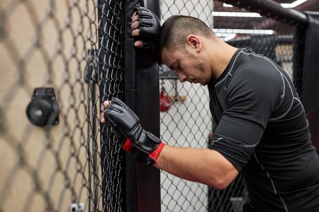 Retrato de jovem cansado encostado na gaiola após um treino duro no ginásio, preciso descansar, olhando para baixo. kickboxing, conceito de mma