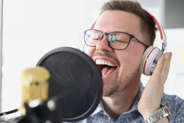 Retrato de jovem cantando em fones de ouvido na frente do microfone no trabalho de estúdio do apresentador na