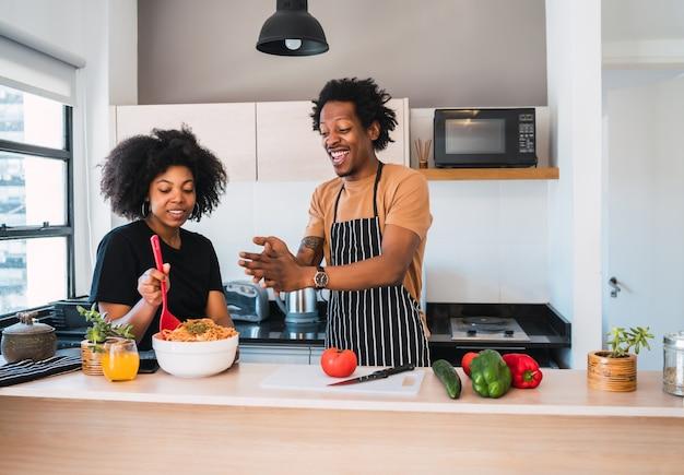 Retrato de jovem casal afro cozinhando juntos na cozinha de casa