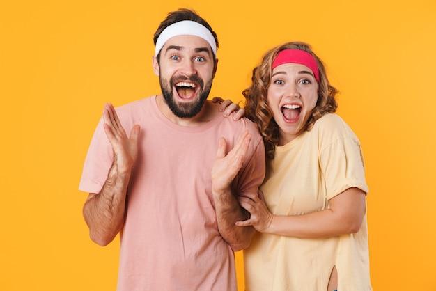 Retrato de jovem casal alegre e atlético usando faixas na cabeça, gritando juntos de surpresa isolado sobre a parede amarela