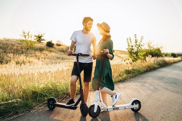 Retrato de jovem casal ao pôr do sol com uma bela paisagem natural. andando em scooters elétricos no campo