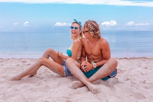Retrato de jovem casal apaixonado na praia e aproveitando o tempo juntos. casal jovem se divertindo em uma costa arenosa.