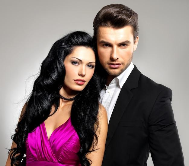 Retrato de jovem casal apaixonado posando no estúdio vestido com roupas clássicas
