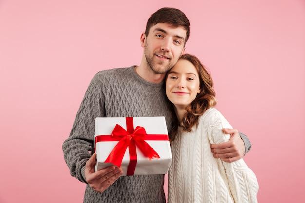 Retrato de jovem casal apaixonado, vestido de camisolas abraçando
