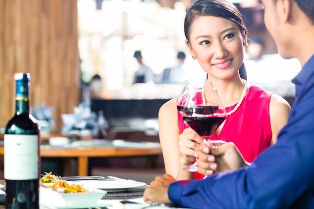 Retrato de jovem casal asiático brindando com vinho