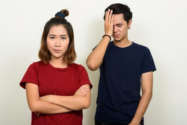 Retrato de jovem casal asiático estressado parecendo chateado depois de uma briga