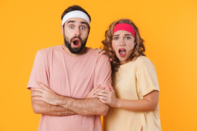 Retrato de jovem casal atlético chocado usando bandanas, gritando e expressando admiração isolado sobre a parede amarela Foto Premium
