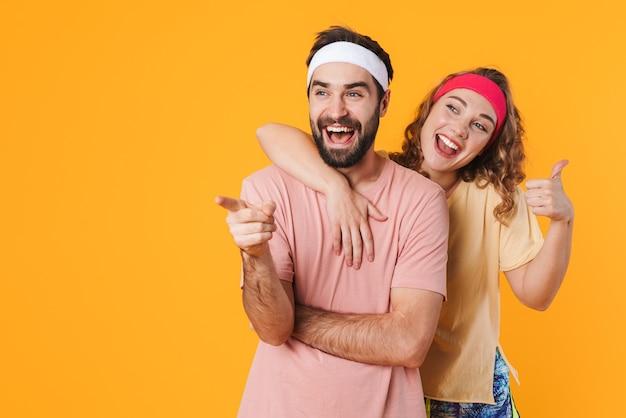 Retrato de jovem casal atlético usando bandanas, sorrindo e gesticulando com o polegar isolado sobre a parede amarela