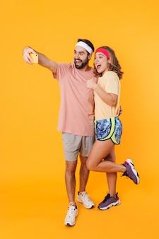 Retrato de jovem casal atlético usando bandanas, sorrindo e tirando uma foto de selfie no celular isolada sobre a parede amarela