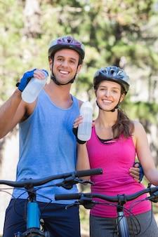 Retrato de jovem casal bebendo água na floresta