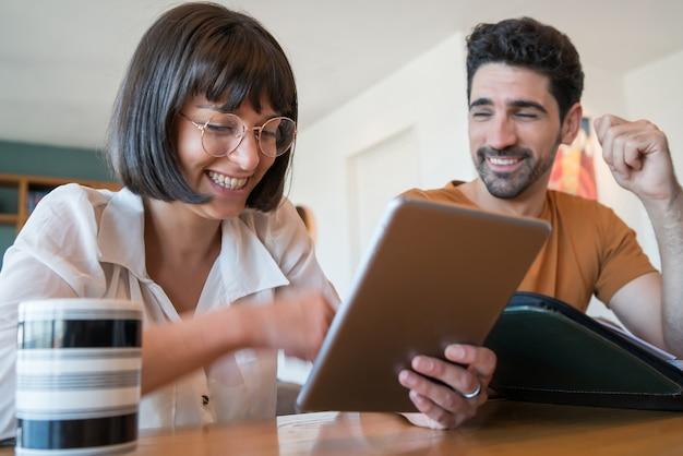 Retrato de jovem casal calculando e pagando contas em um tablet digital em casa